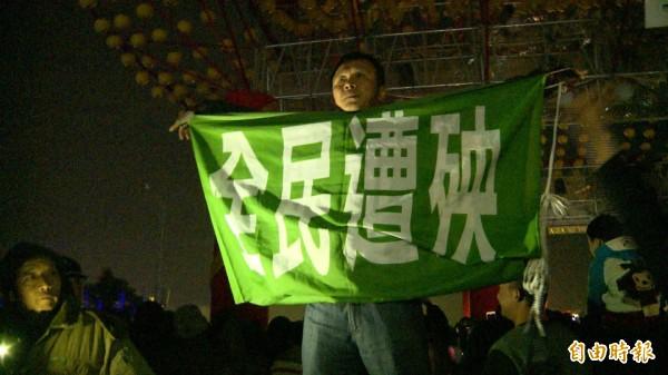 斗南林子里里長黃高明高舉「全民遭殃」布條抗議。(記者廖淑玲攝)