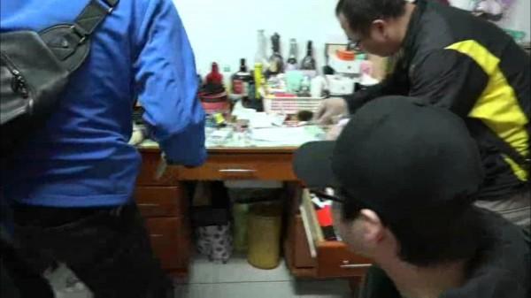 高村世龍(戴黑帽眼睛者)看著警方搜出他的改造槍枝。(記者陳恩惠翻攝)