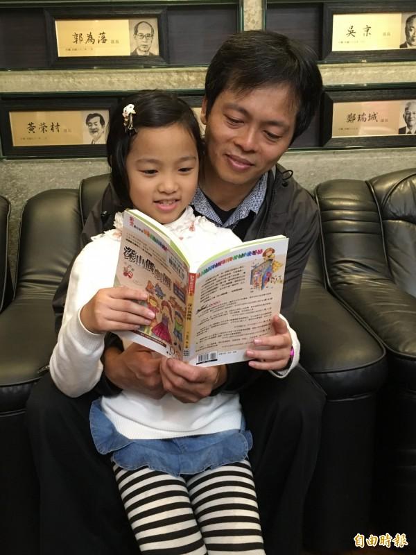 雲林縣9歲孩童李采靜(左),去年借閱3732本書,她表示,自己一天讀12本書,榮獲「兒童組借閱冊數」冠軍。爸爸李憲政(右)陪她北上教育部領獎。(記者林曉雲攝)