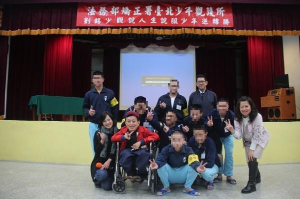 罹患重度小兒麻痺症的劉銘(紅衣者),是「輪椅上的小巨人」,到台北少年觀護所演講,勉勵少年回歸人生正途。(台北少年觀護所提供)