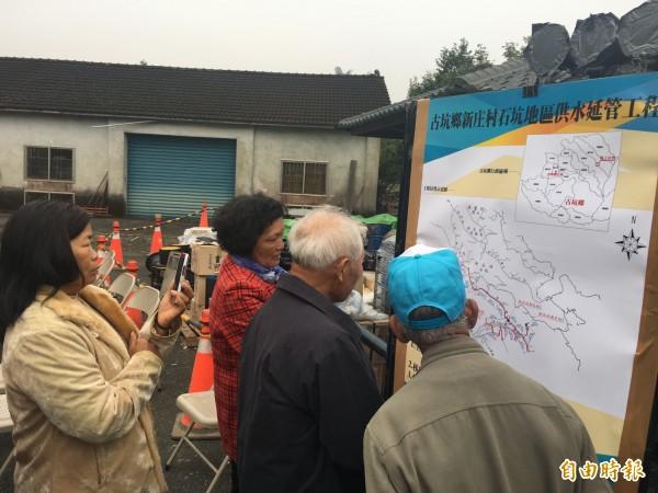 古坑東和新庄山區自來水管延管工程動工,村民仔細查看管線埋設施工圖。(記者黃淑莉攝)