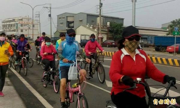 騎上單車追風,自有逍遙遊的快意,不過大家都很有默契的帶上口罩。(記者楊金城攝)
