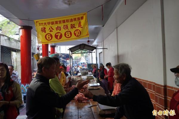 大甲媽在新港奉天宮的祝壽大典結束後,香客們排隊分食祭拜媽祖的豬公肉。(記者曾迺強攝)