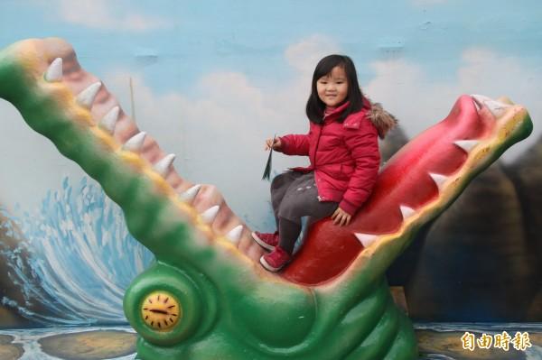 真是驚奇又有趣,雖然這隻鱷魚的嘴巴張得這麼大,看起來怪嚇人的,小朋友還是開心地和裝置藝術合照。(記者林欣漢攝)