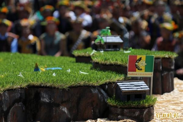由紅、黃、綠三色組成的「百合族旗」為萬山部落族人金紹華設計,代表希望、愛與和平,旗幟上的百合花及鷹羽圖樣,則代表魯凱族的純潔象徵和完整的自然主義。(記者邱芷柔攝)
