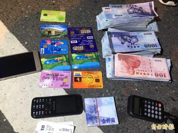 警方在他身上查出大筆贓款,及多張金融卡、金融卡解碼器。(記者王捷攝)