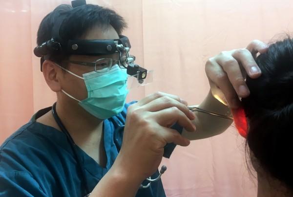 衞福部南投醫院醫師先將甘油球滴入患者的耳道中,靜置5分鐘後,再利用耳鏡和夾子將蛾夾出。(記者謝介裕翻攝)