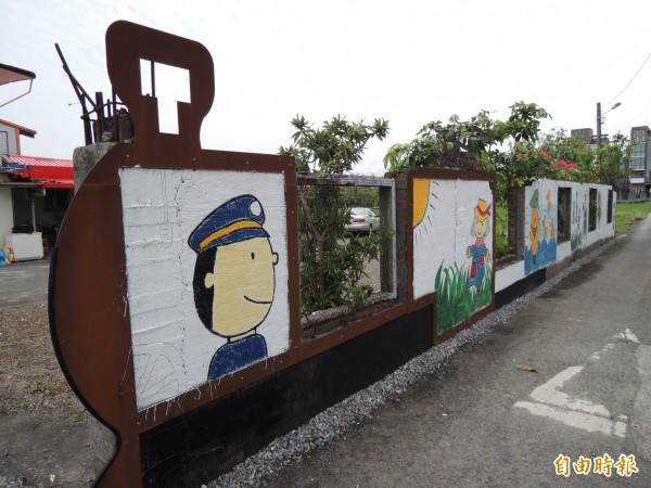 居民在車站附近圍牆彩繪森林小火車圖案。(記者江志雄攝)