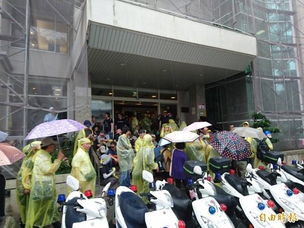 抗議群眾到路旁屋簷下躲雨。(記者王冠仁攝)