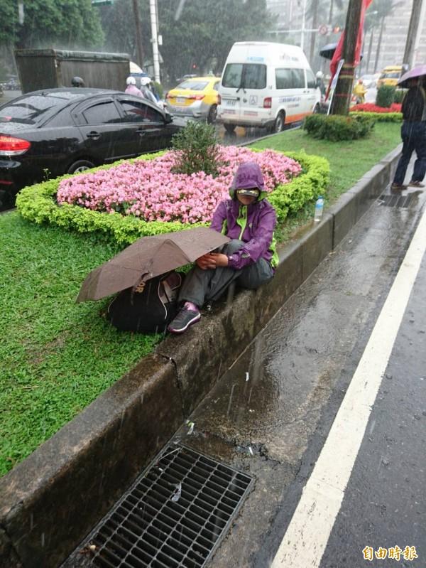 一名抗議群眾坐在中山南路的分隔島上淋雨。(記者王冠仁攝)