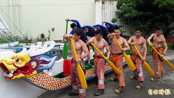 脫掉上衣的消防猛男秀出精實的肌肉,警察型男則強調划龍舟的技術比較重要,現場拿起划槳互尬。(記者洪美秀攝)