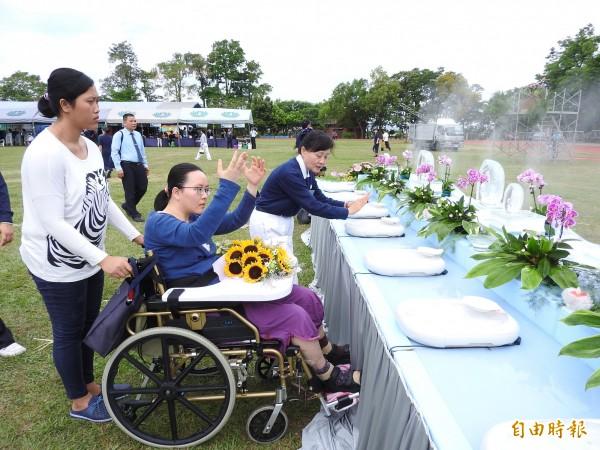 慈濟志工張一賓(右)也推著坐輪椅的女兒劉怡伶虔誠浴佛祈福。(記者佟振國攝)