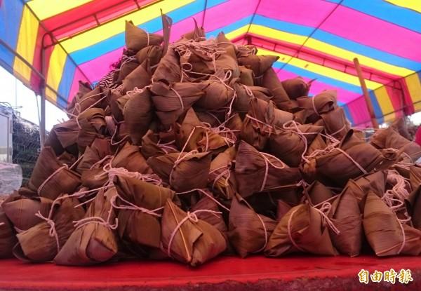 數十名男女老幼今天一起包愛心粽,一上午即包出1700顆,堆疊起來比八卦山還高。(記者湯世名攝)