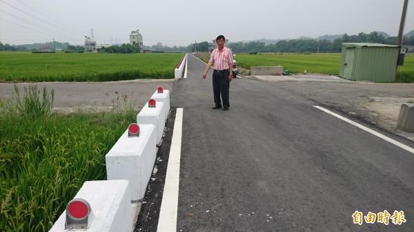 農路改善後,擋土牆(白色護墩)從中段往後開始歪斜,道路愈來愈窄。(記者楊金城攝)