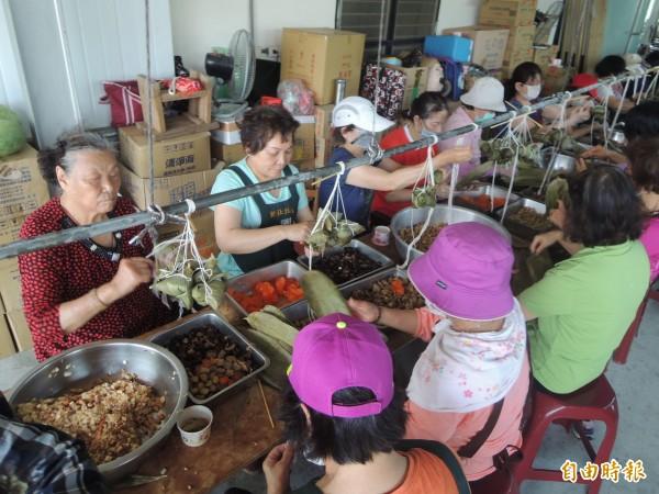 新竹縣竹北市新社社區每年發起端午節關懷活動,今早100多名志工分工合作,捲起衣袖包粽子,將分送弱勢學子、獨居老人和低收入戶。(記者廖雪茹攝)