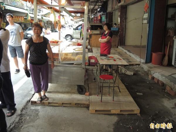 攤商原有水泥平台被拆,改用墊高攤位。(記者翁聿煌攝)