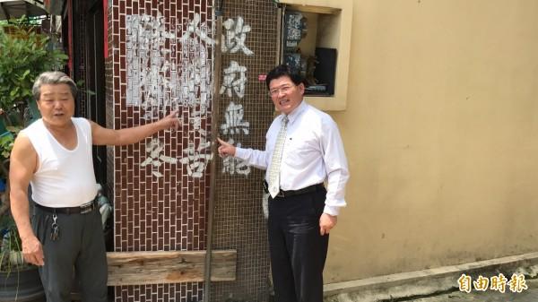 彰化市長邱建富(右)今天到台化街會勘,看到牆上昔日噴漆罵淹水的字樣,居民笑說:「整治後終於不再淹水了。」(記者湯世名攝)