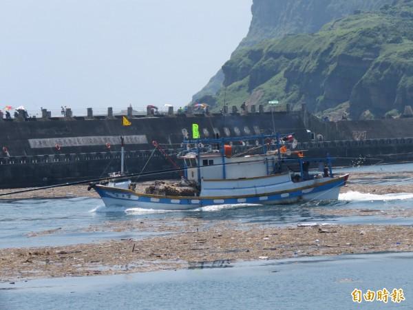 漁船小心翼翼出港,深怕一不小心,引擎、螺旋槳不慎捲入漂流木及垃圾,造成損壞。(記者林欣漢攝)