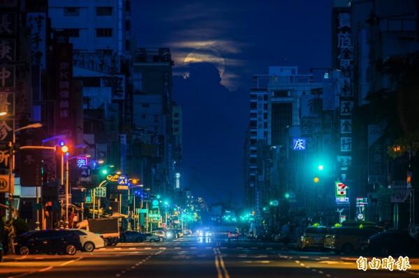 月亮緩緩西下而慢慢被厚厚雲層吞噬。(記者張忠義攝)