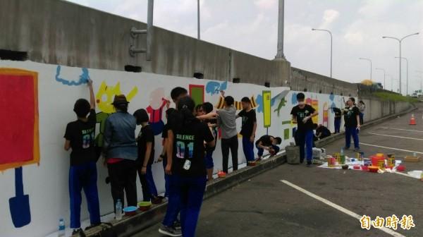 虎尾揚子高中螺陽志工社學生今天彩繪百米牆。(記者廖淑玲攝)