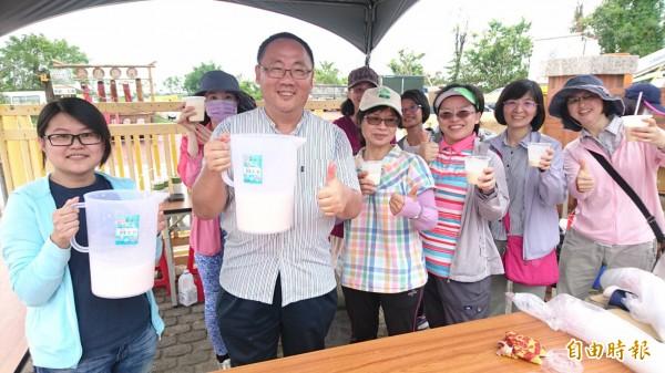 柳營區長李宗翰(前左二)和公所員工招呼遊客免費喝牛奶。(記者楊金城攝)