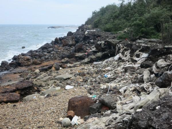 新竹縣竹北、新豐交界處海岸遭濫倒龐大廢棄物,迄今部分太空包破損,有害物質被沖入大海(記者廖雪茹翻攝)