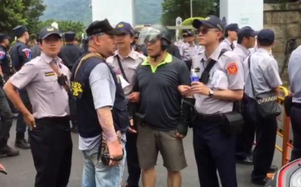 61歲李姓退休警員騎著機車衝向假車隊,丟擲礦泉水瓶,遭警方當場逮捕,訊後依社維法送辦。(記者陳恩惠翻攝)