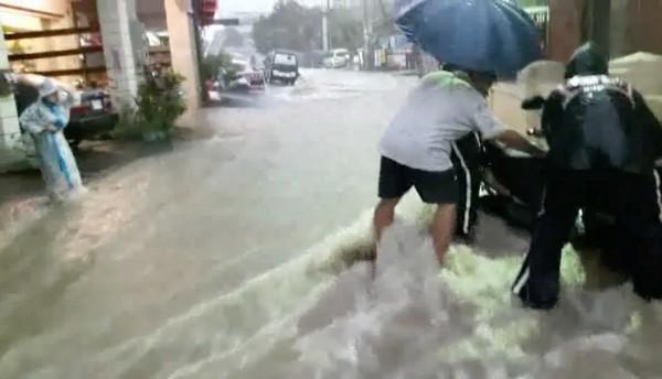 瞬間雷陣雨造成員林市道路變成湍急河道,機車駕駛險被沖走,警察趕緊協助民眾脫困。(記者陳冠備翻攝)