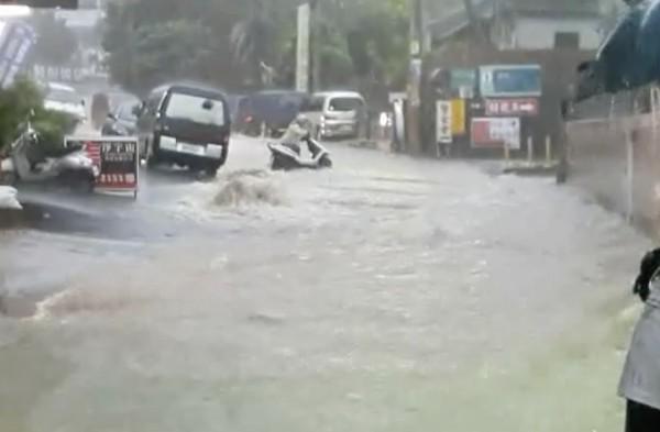 員林市林厝里崙雅巷街道變急流,民眾牽車涉水而過。(記者陳冠備翻攝)