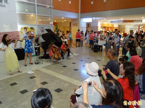美國女音樂家珍妮.鄔克司.貝克(左後一)與家族四名子女訪台公益巡演,在成大醫院大廳快閃演出,吸引民眾觀賞。(記者王俊忠攝)