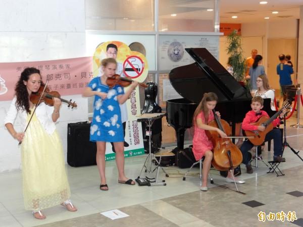 美國女音樂家珍妮.鄔克司.貝克(左一)與家族四名子女訪台公益巡演,在成大醫院大廳快閃演出。(記者王俊忠攝)