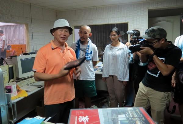 黎明幼兒園園長林金連(左1)解說放映室內的設備。(記者張菁雅攝)