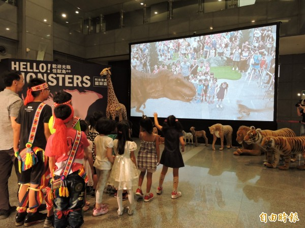 今年新北市兒童藝術節主題為「歡迎光臨怪獸島」,文化局在市府1樓設置全台最大250吋的AR螢幕,引進英國團隊製作的《重返侏儸紀》AR影片,恐龍大軍圍繞玩家身旁,相當逼真。(記者賴筱桐攝)
