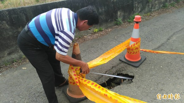 下埤里長洪嘉文丈量坑洞長90公分,請派出所在颱風來臨前先暫時封路,避免造成交通危險。(記者王善嬿攝)