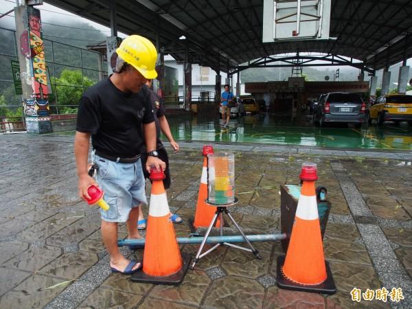 嘉蘭村民在活動中心前擺上雨量監測器,隨時監控雨量狀況。(記者王秀亭攝)