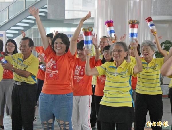 大村鄉擺塘社區的長輩與國際青年志工,一起在員林車站大跳快閃舞。(記者陳冠備攝)