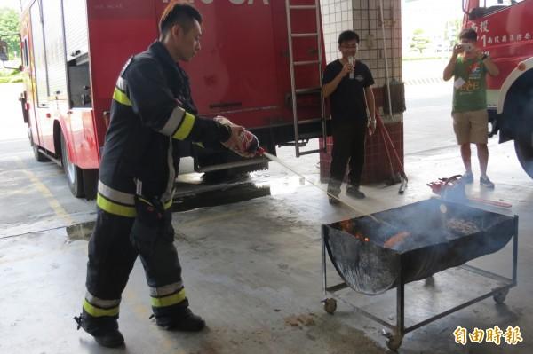 南投縣消防人員進行可樂滅火實驗.,將火勢撲滅。(記者張協昇攝)