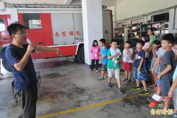 南投縣消防局第一大隊南投分隊長謝濠光告訴前來參加消防體驗的學童說,滅火還是要用滅火器。(記者張協昇攝)