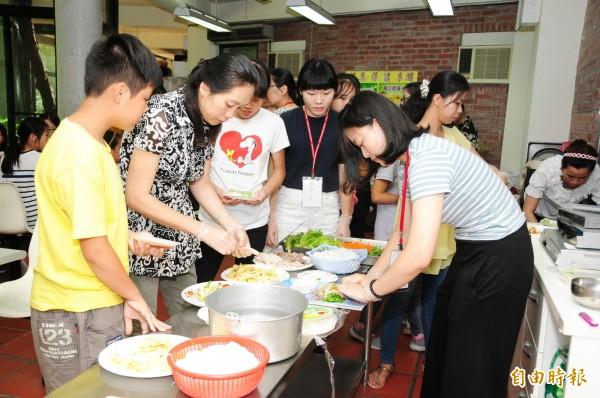 新住民媽媽也與靜宜大學教研所越南籍碩士生,製作傳統越南春捲。(記者張軒哲攝)