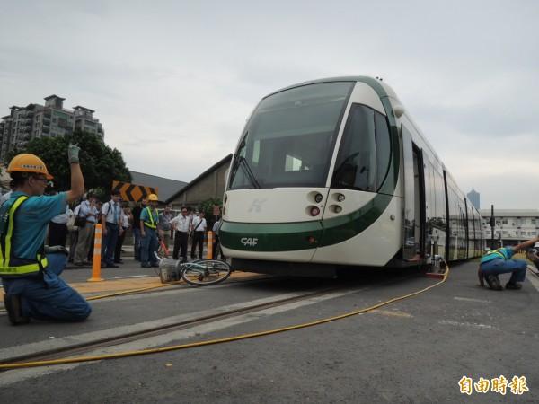 工程人員動用機具將輕軌列車頂起、移出卡在列車下的腳踏車。(記者王榮祥攝)