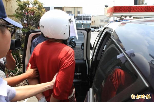 酒後刺傷人的黃男被警方送上警車移送法辦。(記者張聰秋攝)