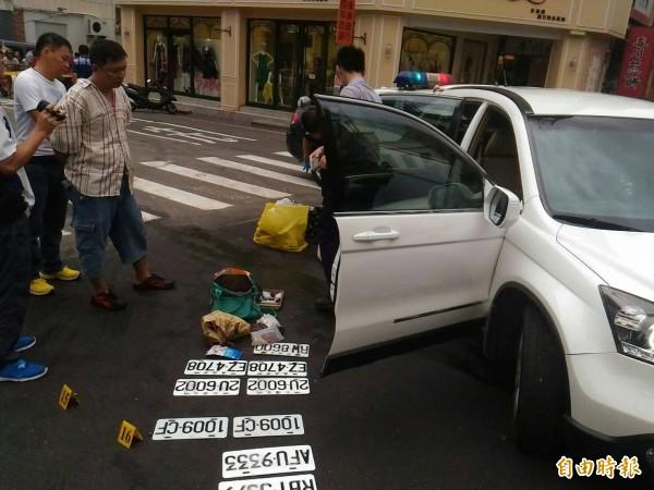 警方從竊嫌羅聖輝(左穿牛仔褲者)駕駛的白休旅車內起出九面車牌與少許安非他命毒品。(記者王俊忠攝)