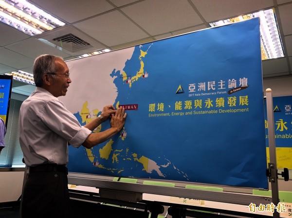 環盟創會會長施信民在地圖貼上台灣。(記者蘇芳禾攝)