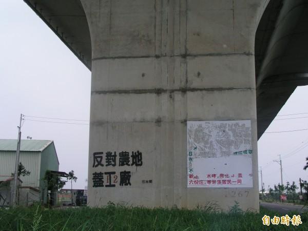 萬丹鄉民在高架橋上噴漆反對農地蓋工廠。(記者葉永騫攝)
