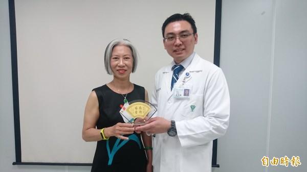 蔡姓婦人(左)贈牌感謝佳里奇美醫院神經外科主治醫師林思維(右)治好她的頸因性頭痛。(記者楊金城攝)