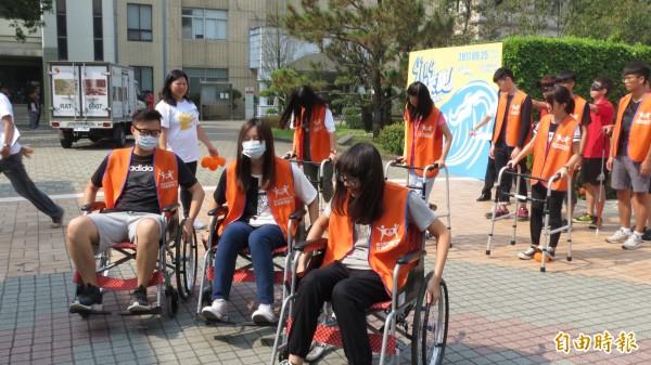 伊甸今天安排50位學生及民眾坐輪椅、戴眼罩走上街道,體會身障者行的不便。(記者蘇金鳳攝)