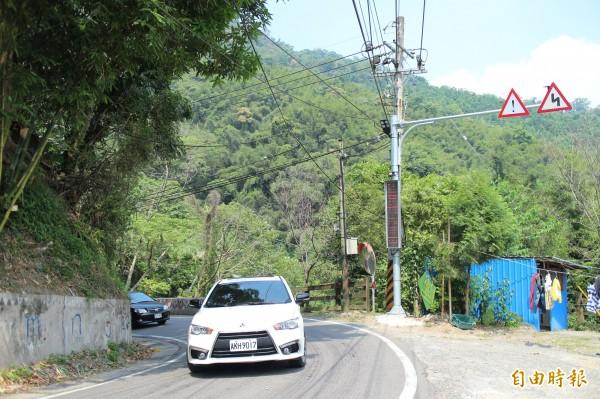 圖中亮起紅字「注意對向來車」警語的「可辨資訊看板」,在對應的車道另外裝有車輛偵測器,有車子通過、偵測到,看板就會亮起紅字,警告來車的對向用路人要注意。(記者黃美珠攝)