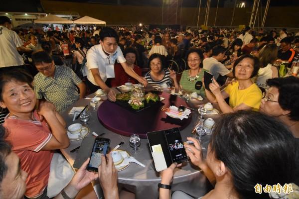 參加千人辦桌的民眾,看到菜餚端上桌,十分開心。(記者李忠憲攝)