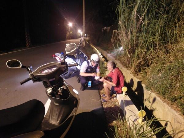 江姓老翁身穿紅衣深夜離家5公里外蹲坐馬路,巡警停車關心並助他返家。(記者李容萍翻攝)