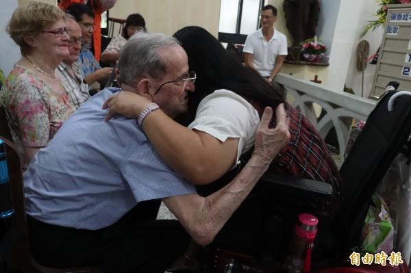 羅文思與自己幫助過的「兒女」們擁抱。(記者林敬倫攝)